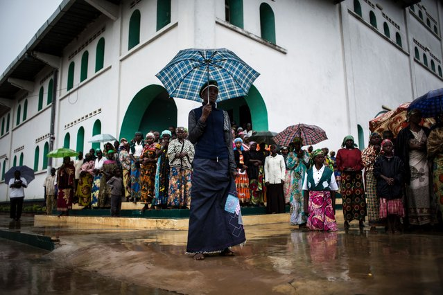Members of the Kimbanguist Church hold umbrellas during their daily morning prayer and lecture session on May 24, 2017 in Nkamba. Entering into the joyous spirit of things, some 4,000 people including elderly, women, teachers, rescue workers and scouts, made a pilgrimage on May 25, 2017 to the holy hill of Nkamba, some 100 kilometres (60 miles) southwest of Kinshasa.  Nkamba is the birthplace of Simon Kimbangu, who launched his ministry in 1921 in an enormous territory which at the time was ruled by Belgium. (Photo by John Wessels/AFP Photo)