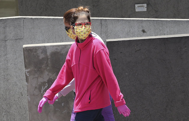 """Women wear face masks and gloves as a precaution against the spread of the new coronavirus, in Quito, Ecuador, Thursday, March 19, 2020. The government has declared a """"health emergency"""", restricting movement to only those who provide basic services, enacting a curfew, and closing schools. (Photo by Dolores Ochoa/AP Photo)"""