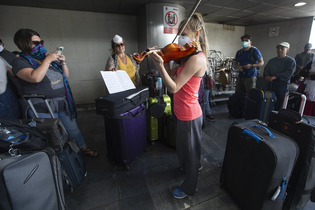 A traveler plays her violin prior to getting on a charter flight coordinated by the U.S. embassy at La Aurora airport in Guatemala City, Monday, March 23, 2020. American citizens stranded abroad because of the coronavirus pandemic are seeking help in returning to the United States. (Photo by Moises Castillo/AP Photo)