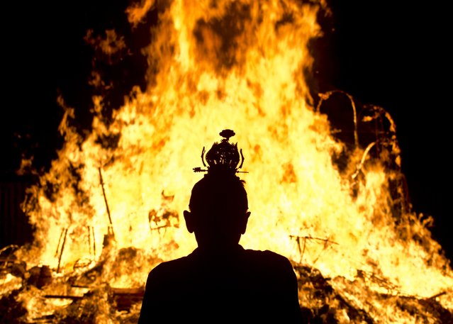 An Ethnic Chinese priest stands in front of statue made of paper of Chinese deity 'Da Shi Ye' or Guardian God of Ghosts set of fire by devotees during the Hungry Ghost festival in Kuala Lumpur,  late on August 10, 2014. (Photo by Manan Vatsyayana/AFP Photo)