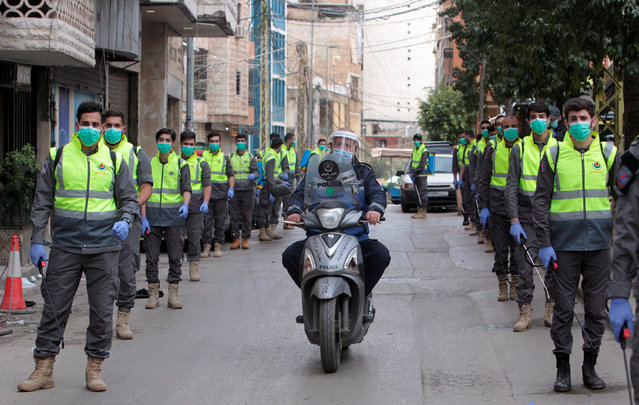 Volunteers from Hezbollah's Islamic health unit stand in preparation to sanitize streets as precaution against the spread of coronavirus disease (COVID-19), during a media tour organised by Hezbollah officials in Beirut's southern suburb, Lebanon March 31, 2020. (Photo by Aziz Taher/Reuters)
