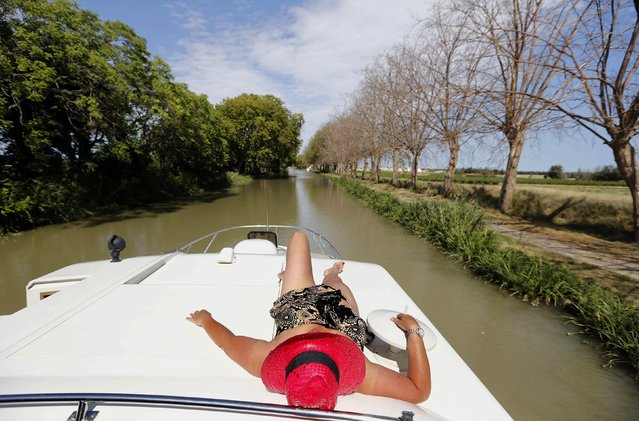 A tourist from Britain takes in the sun on a river boat near Homps along the Canal du Midi, southwestern France, August 12, 2014, during summer holidays. This 360-km network of navigable waterways links the Mediterranean and the Atlantic Ocean through locks, aqueducts, bridges and tunnels. An UNESCO World Heritage site, the Canal du Midi, built between 1667 and 1694, it is a remarkable feat of civil engineering, paving the way for the Industrial Revolution. (Photo by Regis Duvignau/Reuters)