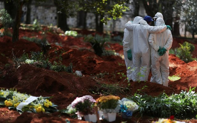 Gravediggers wearing protective suits gather at Vila Formosa cemetery, Brazil's biggest cemetery, during coronavirus disease (COVID-19) outbreak, in Sao Paulo, Brazil, April 2, 2020. (Photo by Amanda Perobelli/Reuters)