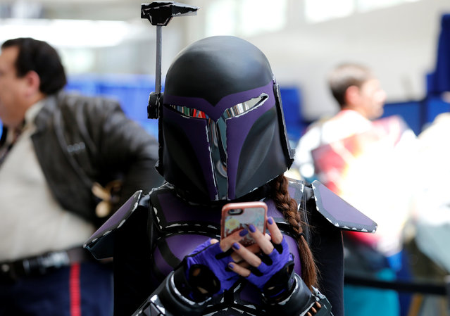 An attendee keeps tabs on her cell phone as she walks the convention floor at the pop culture event Comic-Con International in San Diego, California, United States July 22, 2016. (Photo by Mike Blake/Reuters)