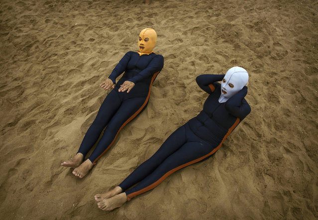 Chinese women wear face-kinis as they exercise on the beach on August 20, 2014 on the Yellow Sea in Qingdao, China. The locally designed mask is worn by many local women to protect them from jellyfish stings, algae and the sun's ultraviolet rays. (Photo by Kevin Frayer/Getty Images)
