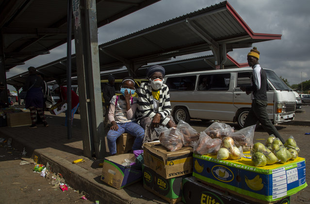 A woman and her daughter wearing face masks to protect against coronavirus, sell fruit and vegetables at the taxi station in Lenasia, south of Johannesburg, South Africa, Wednesday, April 8, 2020. South Africa and more than half of Africa's 54 countries have imposed lockdowns, curfews, travel bans or other restrictions to try to contain the spread of the highly contagious COVID-19 coronavirus. (Photo by Themba Hadebe/AP Photo)