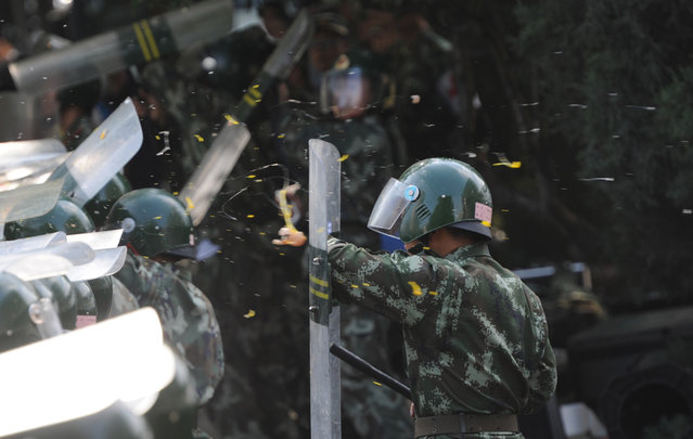 A Chinese riot policeman shields himself from eggs and water bottles thrown by protesters during an anti-Japanese protest outside the Japanese Embassy in Beijing, on September 15, 2012. (Photo by Goh Chai Hin/AFP Photo)