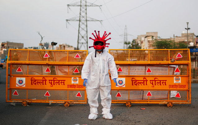 An artist wearing a coronavirus-shaped helmet and a protective suit stands next to a police barricade as he requests people to stay at home during an extended lockdown to slow the spread of the coronavirus disease (COVID-19) in New Delhi, India, April 30, 2020. (Photo by Adnan Abidi/Reuters)
