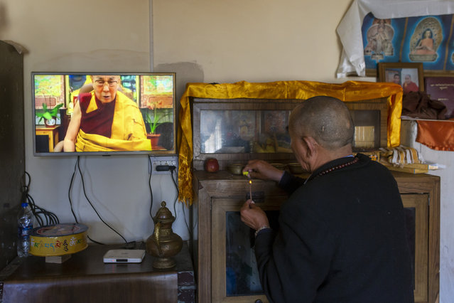 An exile Tibetan lights incense on an altar next to a television showing his spiritual leader the Dalai Lama give a religious talk in Dharmsala, India, Saturday, May 16, 2020. The Tibetan leader spoke to his people through a live web telecast from his residence. This was his first ever appearance after January this year. (Photo by Ashwini Bhatia/AP Photo)