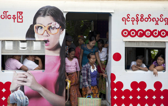 Passengers get off a commuter train painted with advertisement of telecom company Ooredoo upon their arrival at a railway station Wednesday, September 17, 2014, in suburb of Yangon, Myanmar. (Photo by Khin Maung Win/AP Photo)