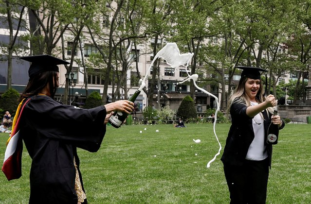 Molloy College Nursing School graduates Taylor Laufer and Yuliya Dubyna make a toast at the center of the lawn in Bryant Park, during the outbreak of the coronavirus disease (COVID-19), in New York, City, New York U.S., May 18, 2020. (Photo by Brendan McDermid/Reuters)