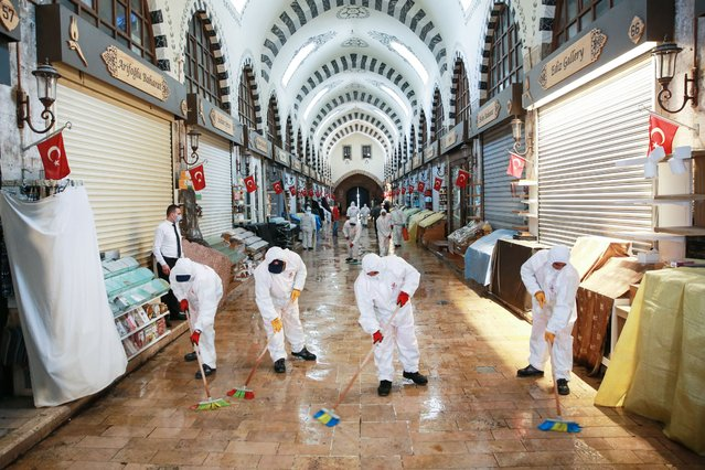 Municipal workers conduct cleaning and disinfection works at Historic Egyptian Bazaar in Istanbul, Turkey on May 28, 2020. The Egyptian Bazaar will open its doors to visitors on June 1 after a hiatus due to the coronavirus (Covid-19) pandemic. (Photo by Ahmet Bolat/Anadolu Agency via Getty Images)