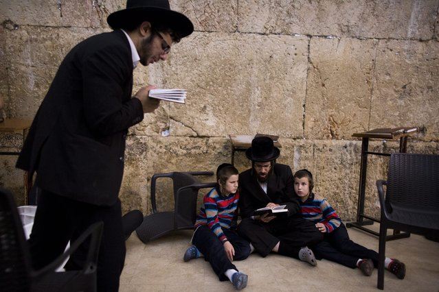 Ultra Orthodox Jews attend a night long prayer with reading from the book of Eicha (Book of Lamentations) to mark Tisha B'av at the Yeshiva at the Western Wall, in Jerusalem, Israel, 13 August 2016. Ultra Orthodox Jews stay up all night and sleep at the Western Wall as they recite lamentations focusing on the destruction of the ancient temple, that was located on the other side of the ancient wall, on the Temple Mount. (Photo by Abir Sultan/EPA)