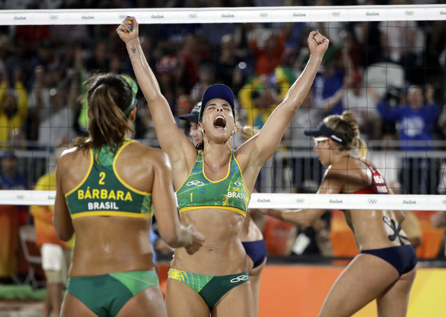 Brazil's Agatha Bednarczuk, center, celebrates a point against the United States with teammate Barbara Seixas de Freitas during a women's beach volleyball semifinal match at the 2016 Summer Olympics in Rio de Janeiro, Brazil, Wednesday, August 17, 2016. (Photo by Marcio Jose Sanchez/AP Photo)