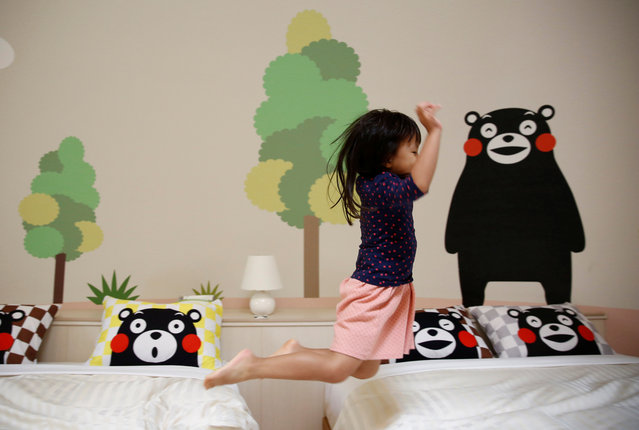 """A girl from Singapore jumps on the bed at a quake-resistant dome house. The head of Aso Farm Land resort, Katsuyuki Kitagawa, designed the dome-shaped cabins after being inspired by his work in the Japanese sweets industry, Konishi said. One day, Kitagawa thought it would be interesting to put people inside """"manju"""" – traditional Japanese sweets that are round and filled with red bean paste – and decided to make rooms shaped like the confection. (Photo by Kim Kyung-Hoon/Reuters)"""