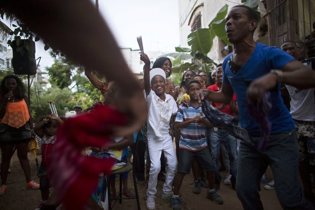 Yensy Villarreal, 9, (C), who lives in Miami, dances in the backyard of his home with friends in celebration for becoming a Santero after passing a year-long rite of passage in the Afro-Cuban religion Santeria, Havana, July 5, 2015. (Photo by Alexandre Meneghini/Reuters)