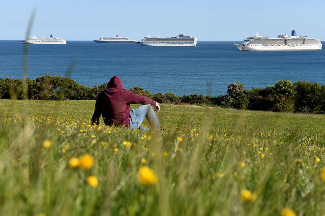 Cruise ships (l-r) MV Aurora, RMS Queen Mary 2, MV Ventura and MV Arcadia anchored in the bay on May 14, 2020 in Weymouth, United Kingdom. The prime minister announced the general contours of a phased exit from the current lockdown, adopted nearly two months ago in an effort curb the spread of Covid-19. (Photo by Finnbarr Webster/Getty Images)