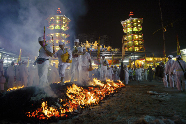 Malaysian ethnic Chinese walk barefoot over burning coals on the final day of the Nine Emperor Gods festival at a temple in Ampang, near Kuala Lumpur, Malaysia, Thursday, October 2, 2014. The men have abstained from meat for the past nine days in order to purify their bodies in preparation for this ritual, in which women are barred from participating. (Photo by AP Photo)