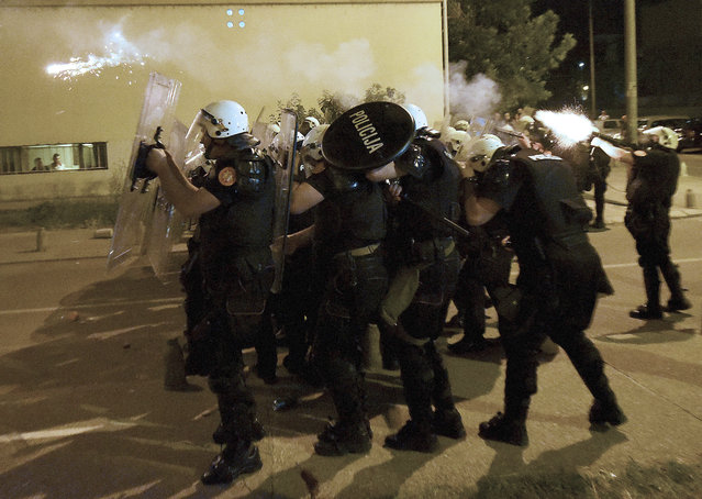 Montenegro police officers fire tear gas during protest in Podgorica, Montenegro, Wednesday, June 24, 2020. Seven police officers were injured and dozens protesters have been detained, including two lawmakers of the Democratic Front, in opposition riots that broke out in several Montenegrin cities on Wednesday. (Photo by Risto Bozovic/AP Photo)