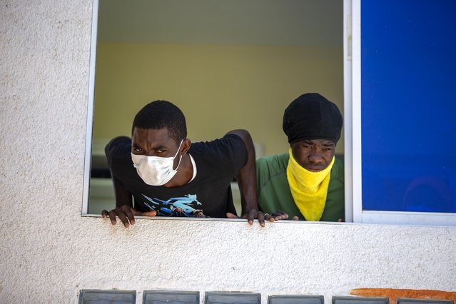 Two men who were deported from the United States and who tested positive for the new coronavirus listen to recommendations given to them by doctors, from the window of the hotel that is used to quarantine them in Tabarre, Haiti, Sunday, April 19, 2020. (Photo by Dieu Nalio Chery/AP Photo)
