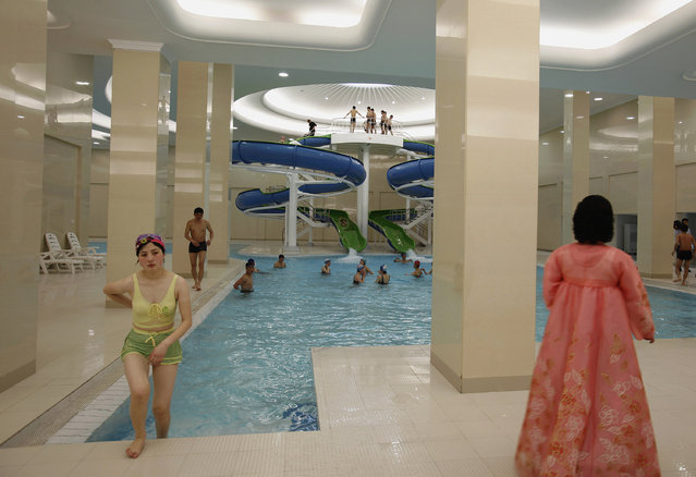 A woman in traditional Korean costume watches as a student leaves a swimming pool of Kim Il-sung University in Pyongyang, April 11, 2012. (Photo by Bobby Yip/Reuters)
