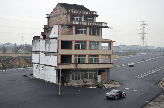 An isolated five-floor building stands in the middle of a new road on November 22, 2012 in Wenling, Zhejiang Province of China. Zhejiang Province of China. 67-year-old Luo Baogen and his 65-year-old wife from Xiazhangyang village still live in the half-demolished residential building, because they are dissatisfied with the relocation compensation. The road, which leads to the Wenling Railway Station, has not been put into use. (Photo by ChinaFotoPress)