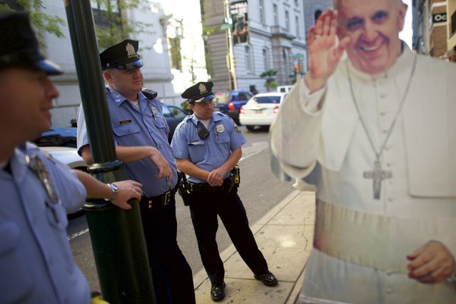 Police officers watch Christa Scalies, (unseen) the co-creator of the Pop-Up Pope, greet pedestrians behind a cardboard cut-out of Pope Francis in Philadelphia, Pennsylvania, September 16, 2015. (Photo by Mark Makela/Reuters)