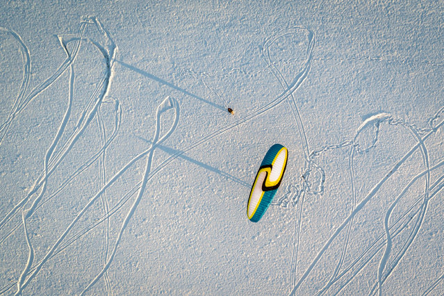 A paraglider has a land-based practice session on snow near Semsales, western Switzerland on December 3, 2017. (Photo by Fabrice Coffrini/AFP Photo)