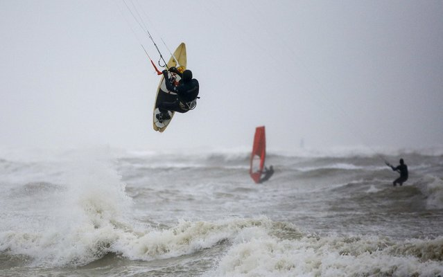 Widsurfers and kitesurfers take advantage of the storm force winds off the coast of West Sussex on December 7, 2017 in Goring, England. Storm Caroline is expected to batter the UK with gusts of up to 90mph and poses a potential risk to life, according to the Met Office. (Photo by Alan Crowhurst/Getty Images)
