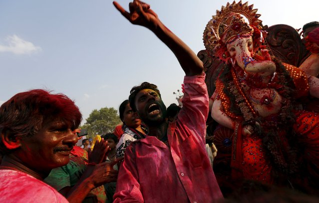 Devotees dance and shout religious slogans as they carry an idol of the Hindu elephant god Ganesh, the deity of prosperity, to be immersed into the polluted waters of the river Yamuna on the last day of the Ganesh Chaturthi festival, in New Delhi, India, September 27, 2015. (Photo by Adnan Abidi/Reuters)