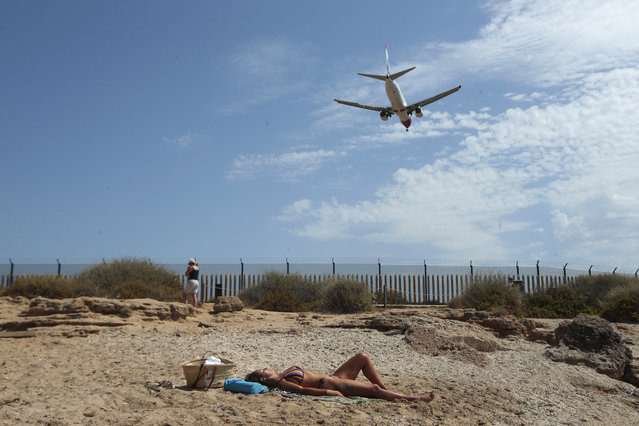 A woman sunbathes on the beach as an airplane lands at the Balearic Islands capital of Palma de Mallorca, Spain, Wednesday, July 29, 2020. Concerns over a new wave of coronavirus infections brought on by returning vacationers are wreaking havoc across Spain's tourism industry, particularly in the Balearic Islands following Britain's effective ban on travel to the country. (Photo by Joan Mateu/AP Photo)