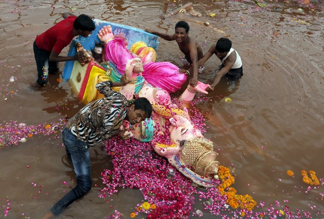 Volunteers push an idol of the Hindu god Ganesh, the deity of prosperity, as they try to remove the idol from a temporary pond after its immersion during the ten-day-long Ganesh Chaturthi festival in Ahmedabad, India, September 22, 2015. (Photo by Amit Dave/Reuters)
