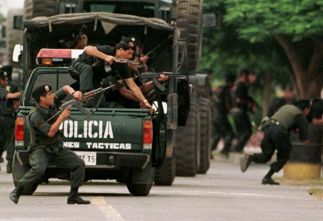 Elite special police run for cover after gunfire was heard from inside the Japanese ambassador's residence in Lima, Peru, January 27, 1997. At the moment the shots were fired, police were parading past the residence in a show of force, and helicopters were flying above. Earlier, several armored personnel carriers rolled past the compound. Tupac Amaru rebels had seized the diplomatic compound December 17 and held 72 hostages. (Photo by Andrew Winning/Reuters)