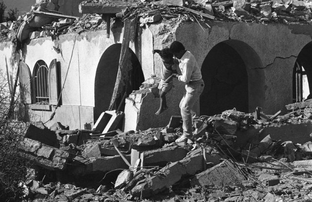 A rescuer lifts a child over the rubble of a destroyed home after six Israeli planes bombed and destroyed the Palestine Liberation Organization headquarters and the surrounding homes killing about sixty people in Hamam Plage, twenty kilometers south of Tunis, Tunisia on Tuesday, October 1, 1985. (Photo by Lionel Cironneau/AP Photo)