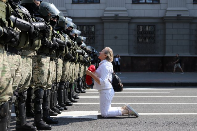 A woman kneels in front of a riot police line as they block Belarusian opposition supporters rally in the center of Minsk, Belarus, Sunday, August 30, 2020. Opposition supporters whose protests have convulsed the country for two weeks aim to hold a march in the capital of Belarus. (Photo by AP Photo/Stringer)