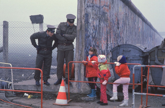 West German school children on their way to school come across the Berlin Wall being opened, and speak with two East German border guards on November 14, 1989 in Berlin, Germany. (Photo By Stephen Jaffe/Getty Images)