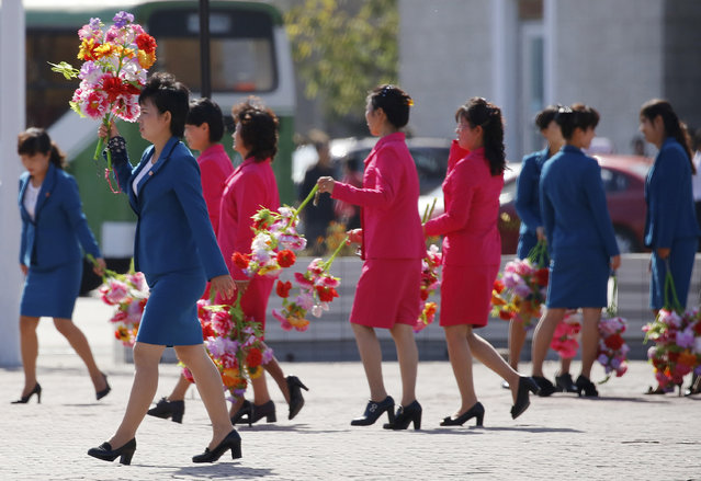 Women walk on a plaza with decorative flowers Friday, October 9, 2015, ahead of Saturday's anniversary celebrations in Pyongyang, North Korea. The country is preparing for the 70th anniversary of the founding of the North Korea Workers' Party on Oct. 10, 2015. (Photo by Charles Dharapak/AP Photo)