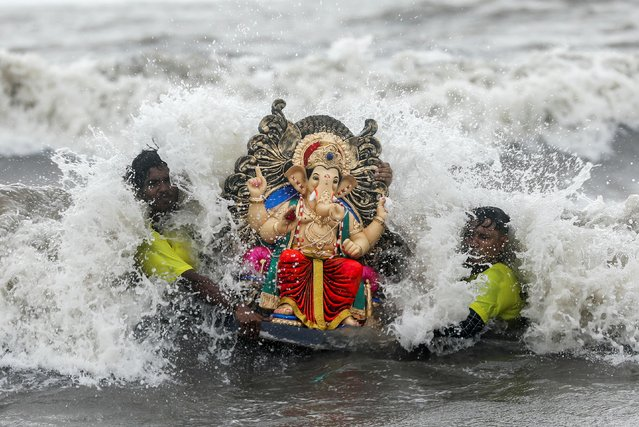 People carry an idol of the Hindu god Ganesh, the deity of prosperity, to immerse it off the coast of the Arabian sea during the Ganesh Chaturthi festival in Mumbai, India, August 23, 2020. (Photo by Francis Mascarenhas/Reuters)