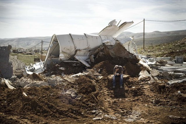 An Israeli settler sits praying among the rubble of his house that was demolished by Israeli police in the outpost of Maale Rehavam, in the Israeli occupied Palestinian West Bank, on February 13, 2013. The house was built without any authorization outside the larger state-sanctioned settlement. The number of Israeli settlers in the occupied West Bank grew by 4.7% in 2012, according to figures obtained by AFP from a settler organisation. (Photo by Janos Chiala/AFP Photo)