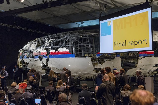 The reconstructed airplane serves as a backdrop during the presentation of the final report into the crash of July 2014 of Malaysia Airlines flight MH17 over Ukraine, in Gilze Rijen, the Netherlands, October 13, 2015. The Dutch Safety Board, issuing long-awaited findings on Tuesday of its investigation into the crash of a Malaysian passenger plane over eastern Ukraine, is expected to say it was downed by a Russian-made. (Photo by Michael Kooren/Reuters)