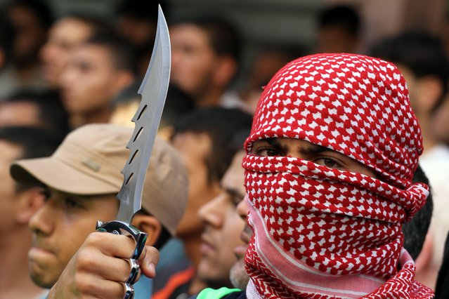 A Palestinian man holds a knife during an an anti-Israel protest in Jabalia in the northern Gaza Strip. The unrest that has engulfed Jerusalem and the occupied West Bank, the most serious in years, has claimed the lives of 34 Palestinians and seven Israelis. The unrest has been triggered in part by Palestinians' anger over what they see as increased Jewish encroachment on Jerusalem's al-Aqsa mosque compound. (Photo by Mohammed Asad/APA Images via ZUMA Wire)