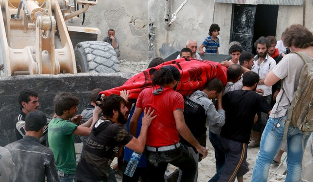 Search and rescue team members carry a dead body from debris of a building after warcrafts belonging to Syrian and Russian army carried out an airstrike on opposition controlled residential area at Merce neighborhood of Aleppo, Syria on September 23, 2016. (Photo by Jawad al Rifai/Anadolu Agency/Getty Images)