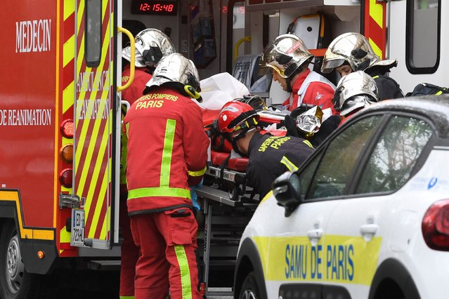 French firefighters load an injured person into a waiting ambulance near the former offices of the French satirical magazine Charlie Hebdo following an alleged attack by a man wielding a knife in the capital Paris on September 25, 2020. The threats coincide with the trial of 14 suspected accomplices of the perpetrators of the massacres at Charlie Hebdo and a Jewish supermarket that left a total of 17 dead. (Photo by Alain Jocard/AFP Photo)