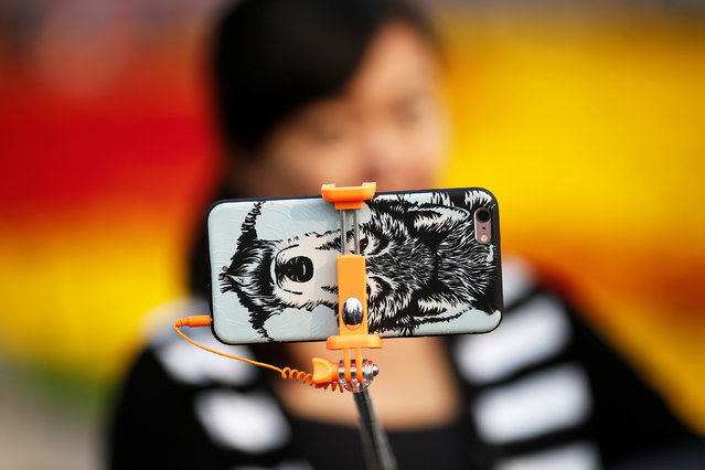 A woman takes pictures of herself as people gather in Tiananmen Square to celebrate National Day marking the 67th anniversary of the founding of the People's Republic of China, in Beijing October 1, 2016. (Photo by Damir Sagolj/Reuters)