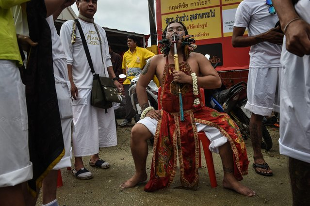 A devotee of the Nine Emperor Gods is seen with multiple skewers in his face during the annual Phuket Vegetarian Festival in the southern province of Phuket on October 3, 2016. (Photo by Lillian Suwanrumpha/AFP Photo)