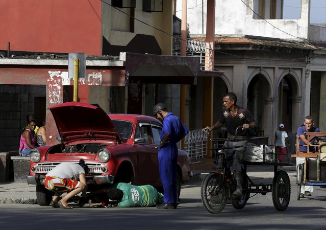 Cubans repair a car on a street in Havana October 27, 2015. (Photo by Enrique De La Osa/Reuters)