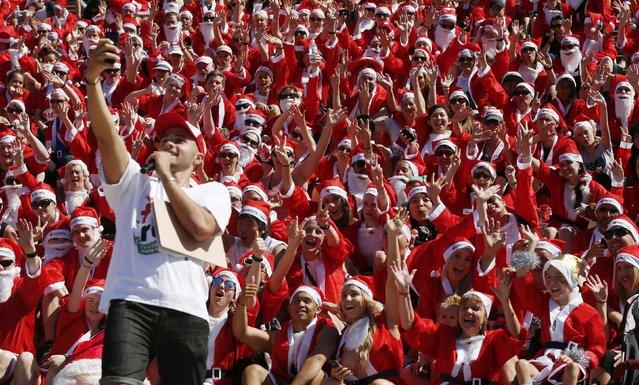 An event announcer takes a 'selfie' with thousands of runners in Father Christmas suits after completing an annual Santa fun run from Darling Harbour to the Sydney Opera House, December 7, 2014. (Photo by Jason Reed/Reuters)