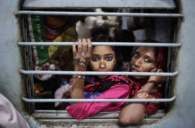 In this November 18, 2014 photo, Murshida, 12, sits on the lap of her mother Marjina as the train leaves for their village in West Bengal, at a railway station in New Delhi, India. Six months ago, Marjina stepped off a train in New Delhi with her two children, hoping to find a better life after her husband abandoned them without so much as a goodbye. (Photo by Altaf Qadri/AP Photo)