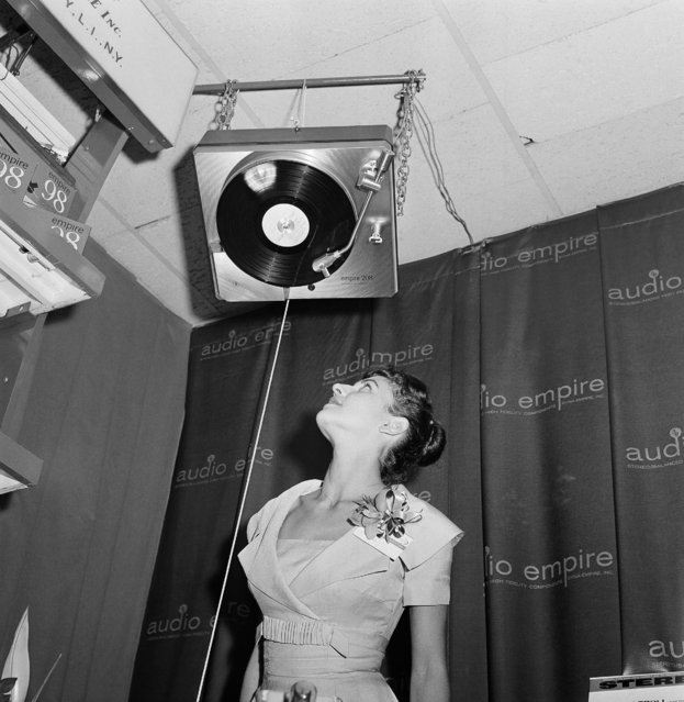 Even upside down, a stereophonic turntable continues to play and  hold the interest of Helen Sorowitz, a visitor to the New York High Fidelity Show in New York, September 9, 1960. (Photo by Ruben Goldberg/AP Photo)