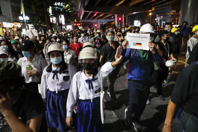 """Pro-democracy protesters flashing three fingers as they march to the German Embassy in central Bangkok, Thailand, Monday, October 26, 2020. As lawmakers debated in a special session in Parliament that was called to address political tensions, student-led rallies were set to continue with a march through central Bangkok on Monday evening to the German Embassy, apparently to bring attention to the time King Maha Vajiralongkorn spends in Germany. The sign translated reads, """"People see you in Germany"""". (Photo by Gemunu Amarasinghe/AP Photo)"""
